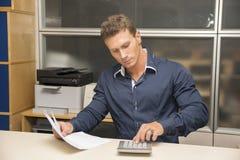 Employé de bureau de sexe masculin bel à l'aide de la calculatrice image stock