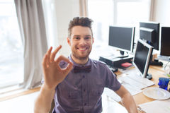 Employé de bureau de sexe masculin créatif heureux montrant le signe correct Image stock