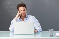 Employé de bureau de sourire avec l'ordinateur Photo stock