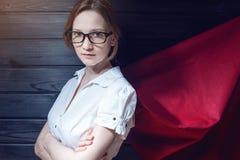 Employé de bureau de superwoman se tenant dans un costume et un manteau rouge photo stock