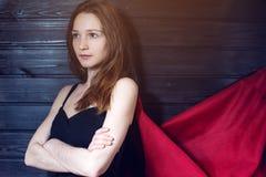 Employé de bureau de superwoman se tenant dans un costume et un manteau rouge images libres de droits
