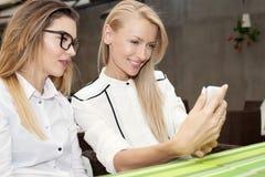 Employé de bureau deux regardant le téléphone portable Image libre de droits