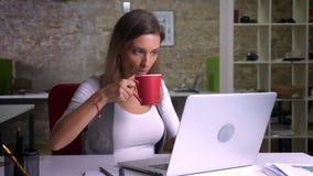 Employé de bureau féminin adulte attirant dactylographiant sur l'ordinateur portable et le café potable sur le lieu de travail à  clips vidéos