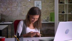 Employé de bureau féminin attirant s'asseyant devant l'ordinateur portable, la transmission de messages au téléphone et rire banque de vidéos