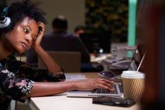 Employé de bureau féminin avec du café au bureau fonctionnant tard Photos libres de droits