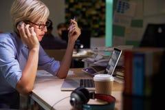 Employé de bureau féminin avec du café au bureau fonctionnant tard Image stock