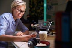 Employé de bureau féminin avec du café au bureau fonctionnant tard Photos stock