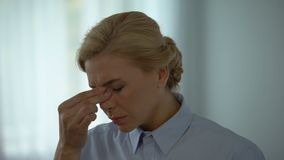 Employé de bureau féminin enlevant des verres, la douleur oculaire se sentante, l'effort et l'épuisement banque de vidéos