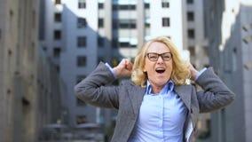 Employé de bureau féminin heureux célébrant le geste d'oui d'apparence de succès, accomplissement clips vidéos