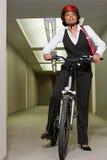 Employé de bureau féminin sur un vélo de montagne photo stock