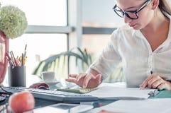 Employé de bureau Jeune femme d'affaires à l'aide de la calculatrice et de l'ordinateur portable f image stock