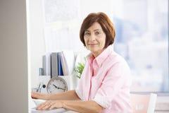 Employé de bureau mûr s'asseyant au bureau images libres de droits
