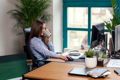 Employé de bureau prenant une pause-café avec une tasse d'expresso dans des ses mains photos stock