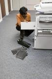Employé de bureau regardant le photocopieur photographie stock libre de droits