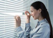 Employé de bureau regardant par des abat-jour de fenêtre Photos libres de droits