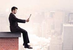 Employé de bureau s'asseyant sur le dessus de toit dans la ville Photographie stock
