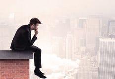 Employé de bureau s'asseyant sur le dessus de toit dans la ville Image stock