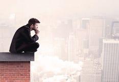Employé de bureau s'asseyant sur le dessus de toit dans la ville Photo libre de droits