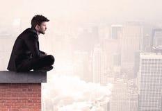 Employé de bureau s'asseyant sur le dessus de toit dans la ville Images libres de droits