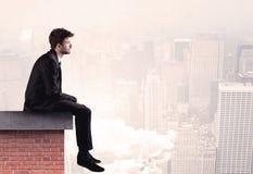 Employé de bureau s'asseyant sur le dessus de toit dans la ville Images stock