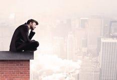 Employé de bureau s'asseyant sur le dessus de toit dans la ville Photographie stock libre de droits