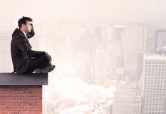 Employé de bureau s'asseyant sur le dessus de toit dans la ville Image libre de droits
