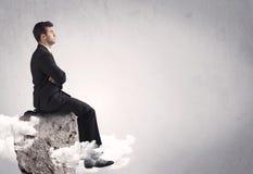 Employé de bureau s'asseyant sur une roche Photos stock