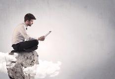 Employé de bureau s'asseyant sur une roche Photo stock