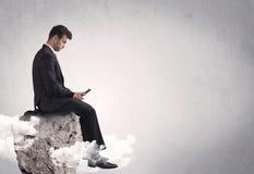 Employé de bureau s'asseyant sur une roche Image stock