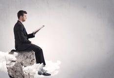 Employé de bureau s'asseyant sur une roche Images libres de droits