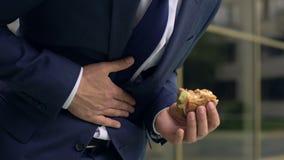 Employé de bureau sentant le malaise abdominal tout en mangeant l'hamburger malsain banque de vidéos