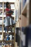 Employé de bureau sur l'échelle dans la chambre de stockage de fichier Images stock
