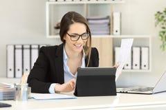 Employé de bureau travaillant comparant des documents sur le comprimé image stock
