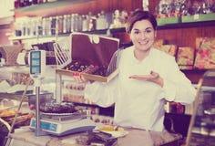 Employé de magasin démontrant la boîte de chocolats Photographie stock