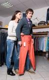 Employé de magasin montrant des jeans à l'homme Images libres de droits