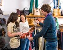Employé de magasin montrant des sacs à de belles femmes Photo stock