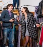 Employé de magasin montrant le manteau à la belle femme Photo libre de droits