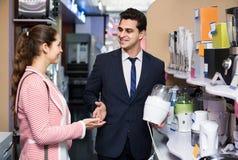 Employé de magasin travaillant avec le client Photo stock