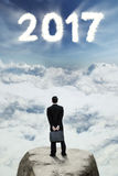 Employé envisageant le nouvel avenir 2017 sur la roche Images stock