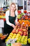 Employé féminin d'épicerie vendant les fruits saisonniers Photos libres de droits
