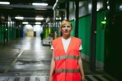 Employé féminin dans un gilet orange de robe longue dans l'espace de fonctionnement des installations productives Photo libre de droits