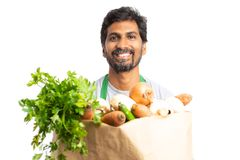 Employé indien masculin tenant le sac de papier avec des épiceries photos libres de droits