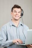 Employé masculin de centre d'appels à l'aide de l'ordinateur portable Images stock