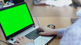 Employé masculin travaillant sur l'ordinateur portable avec l'écran vert au bureau fonctionnant dans le bureau clips vidéos
