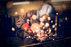 Employé rectifiant en acier avec des étincelles photographie stock libre de droits