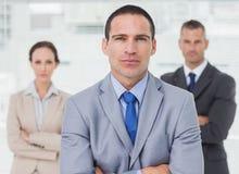 Employé sérieux posant avec ses collègues sur le fond images stock