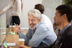 Employé supérieur de sourire discutant l'email avec le collègue africain Photos stock