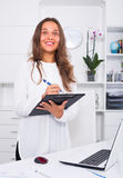 Employée de jeune femme dans le bureau Photos stock