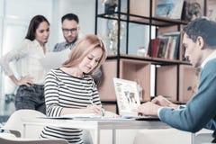 Employés élégants agréables s'asseyant et travaillant ensemble Photographie stock libre de droits