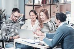 Employés élégants jolis à l'aide de l'ordinateur portable et écoutant le collègue Image libre de droits